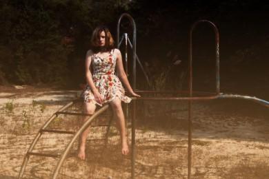 une fille perchée sur une vieille structure de jeu rouillée