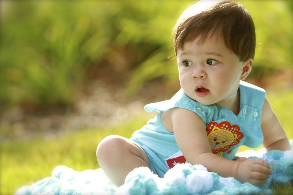 photo bébé petit garçon dans l'herbe
